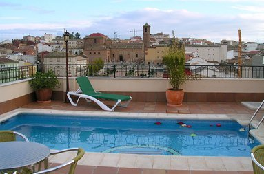 The outdoor pool on the terrace of the hotel is ...